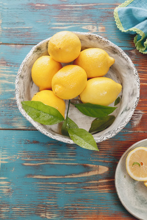 lemon: Lemons. Fresh lemons with leaves in  rustic ceramic bowl over wooden background. Macro selective focus vintage style. Natural light