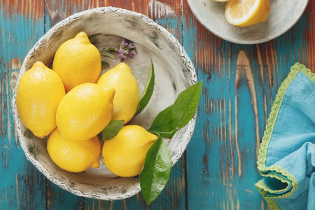 Lemons. Fresh lemons with leaves in  rustic ceramic bowl over wooden background. Macro selective focus vintage style. Natural light