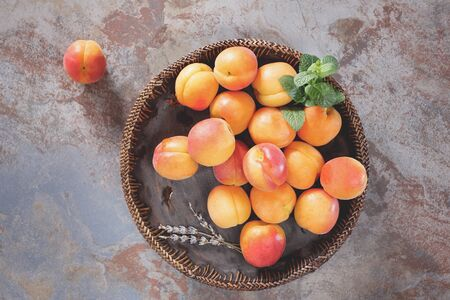 lavender: Bowl of harvested apricots.  Fresh apricots in wooden bowl on old rustic background decorated with mint and lavender flower. Top view rustic style. Natural light Stock Photo