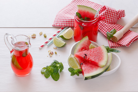 sliced watermelon: Fresh Watermelon With juice and pistachio.   Watermelon fruit drink with pistachio mint and lime and  fresh watermelon slice in heart shape bowl. .Macro selective focus natural light Stock Photo