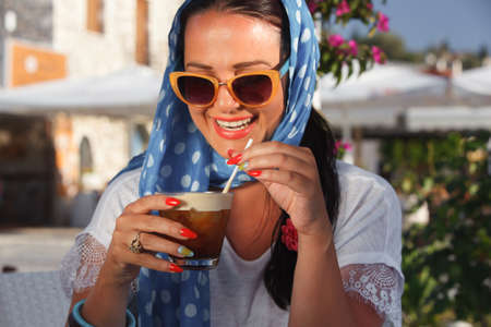 capuchino: Happy young woman smiling and drinking iced coffee in restaurant. Vintage style. Soft focus. Focus on the glass of ice  coffee