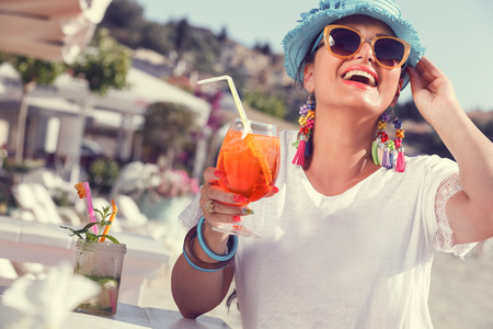 Happy young woman  holding a glass of cocktail near the yacht marine. Selective focus Standard-Bild