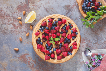 Berry pie. Whole homemade mixed berry lattice top pie on rustic table, top view