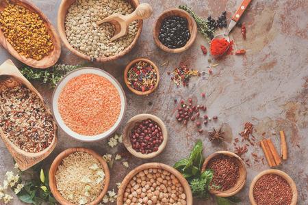 豆類、穀物、種の品揃え。穀物、米、マメ科植物スパイス、素朴なテーブルの上面上の鉢にハーブ各種
