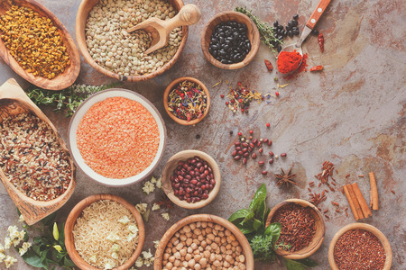Assortiment de légumineuses, de céréales et de graines. Différents types de céréales, le riz, les légumineuses épices et des herbes dans des bols sur la table rustique, vue de dessus