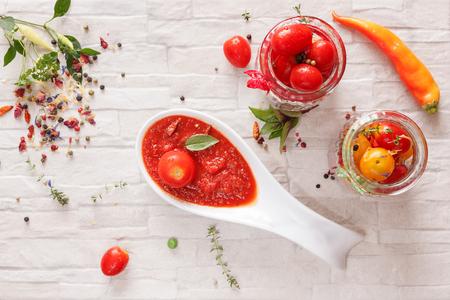 salsa de tomate: mermelada de tomate. mermelada de tomate picante en la cuchara y tomates frescos en un frasco de vidrio, vista desde arriba