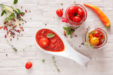 Tomato jam. Spicy tomato jam  on spoon and fresh tomatoes in a glass jar, top view