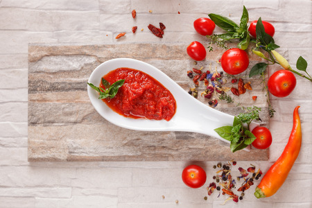 chutney: Tomato chutney with ingredients. Tomato and roasted pepper chutney on spoon, top niew