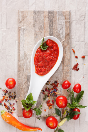 Tomato chutney with ingredients. Tomato and roasted pepper chutney on spoon, top niew