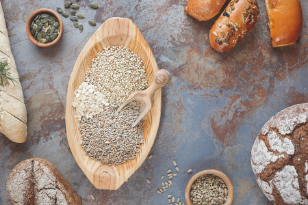 seeds of various: Grain breads and cereals. Various kinds of bread, bread rolls and seeds for baking. Ingredients for bread preparation, top view, vintage style