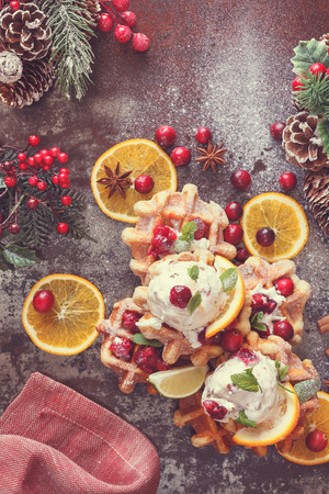 sweet treat: Cranberry waffles with orange ice cream  in a Christmas setting.  Homemade  waffles with  cranberries served with orange ice cream. Top view, blank space, vintage toned