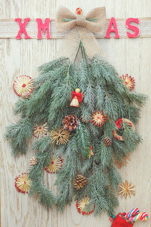 lettre s: Christmas background. Christmas winter background with snow covered evergreen branches, natural straw star ornaments  and XMAS letters on top. Top view,  vintage toned image