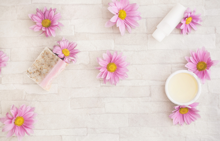 skincare products: Natural  skincare products and  ingredients. Spa still life with soap, facial mask and scented oil with chrysanthemum flowers. Overhead view with blank space