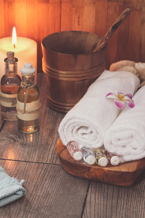scented candle: Spa treatment setting with frangipani, essential oil, scented candle  and towels for spa.  Macro selective focus with retro style processing, blank space Low light spa setting Stock Photo