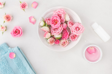 aroma bowl: Spa settings with roses. Fresh roses and rose petals in a bowl of water and various items used in spa treatments