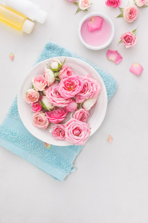 used items: Spa settings with roses.  Fresh roses and rose petals in a bowl of water and various items used in spa treatments Stock Photo