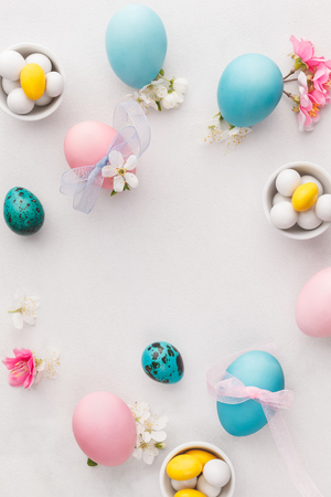 Easter eggs. Various pastel colored Easter eggs, candies and decorations.   Macro, selective focus, top view, blank space