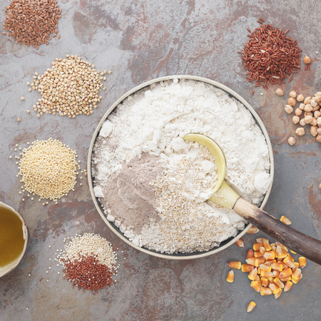 Gluten Free Baking. Overhead view of bowl with flour and grains next to bowl  on table Imagens
