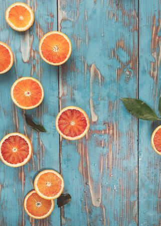 Blood oranges halved. Halved blood oranges scattered on a turquoise rustic board. Top view, vintage toned image, blank space Standard-Bild