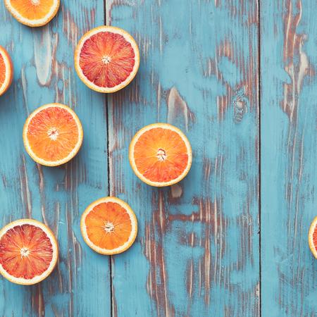 Blood oranges halved. Fresh  blood orange halves on turquoise board. Top view, vintage toned image, blank space