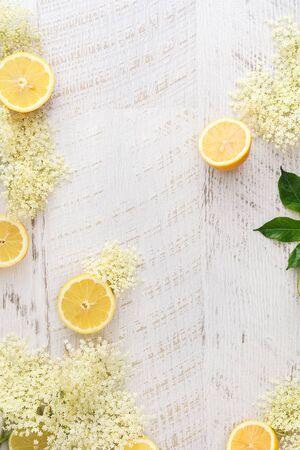 Elderflowers and lemons on a wooden surface.  Ingredients for elder flower syrup, rustic wood background. Top view, blank space