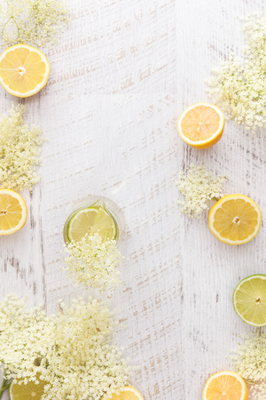 cordial: Elderflower cordial and ingredients.  Homemade elder flower cordial with lemons and elderflowers  on a rustic table. Top view with copyspace in the middle