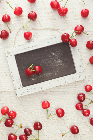 scattered in heart shaped: Red cherries scattered on rustic table and heart shaped pair of cherries on empty chalkboard. Overhead view, blank space