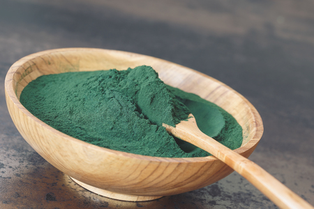 Spirulina Algae Powder, close up. Spirulina powder in wooden bowl with spoon. Macro, selective focus, blank space Standard-Bild