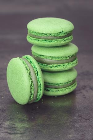 Green macaron. A stack of green tea  macaron on rustic background.   Macro, selective focus, vintage toned image