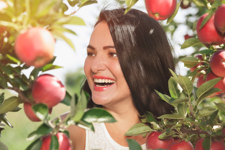 ida: Beautiful woman standing  in her organic apple orchard, close up, selective focus Stock Photo