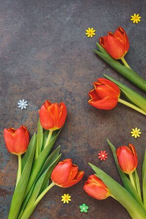 top seven: Easter Tulips and sugar small flower sprinkles on the background of stone surface, top view, copy space