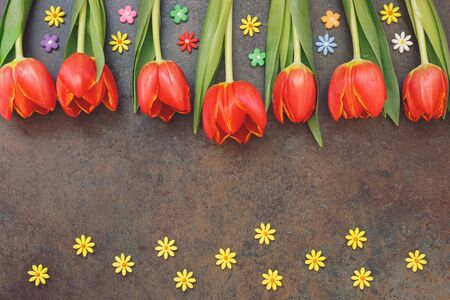 top 7: Easter composition with  tulips and sugar small flower sprinkles on the background of stone surface, top view, copy space Stock Photo