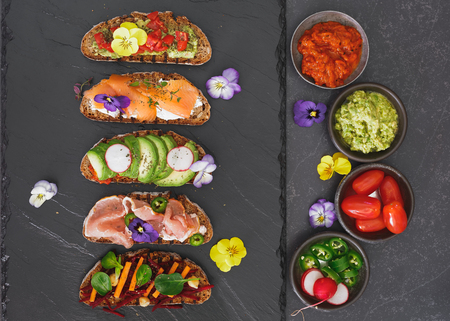 edible: Spring tea sandwiches with flowers and herbs. Top view, blank space