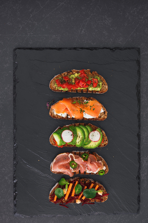Open rye bread sandwiches topped with salmon, avocado, beetroot, cream cheese, prosciutto and other ingredients. Top view, blank space