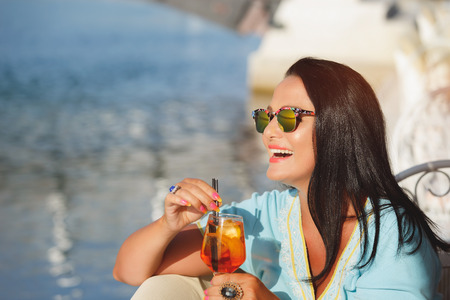 Beautiful  brunette woman sitting at seaside cafe and enjoying a cocktail with a orange twist, selective focus Stock Photo