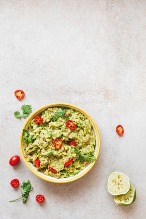 table top: Bowl of guacamole dip with ingredients. Rustic background, top view, lots of copy space