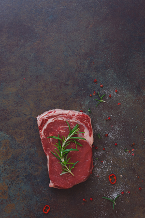 table top: Raw beef steak garnished with rosemary, awaiting the oven. Rustic background, top view, lots of copy space