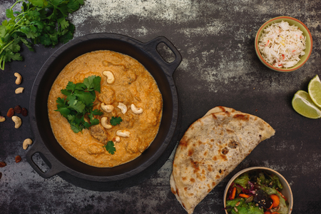 Mutton Korma, Indian curry meal with  nuts, rice and peshwari naan, top view, blank space