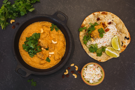 Indian curry meal, lamb korma with cashew nuts, rice and peshwari naan, top view, blank space