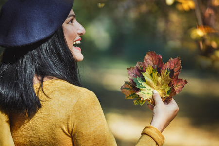 Woman enjoying the fall season in a forest, selective focus Stock Photo