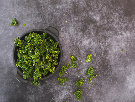 Kale chips with salt in a bowl on dark background. Top view, blank space 스톡 콘텐츠