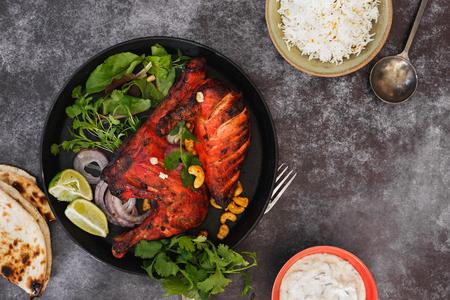 Tandoori chicken  with spicy pilau rice, peshwari naan  and raita. Top view, blank space