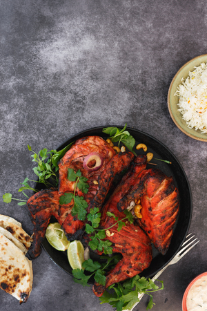 Tandoori chicken. Half of tandoori chicken  served with lime slices and cilantro. Top view, blank space