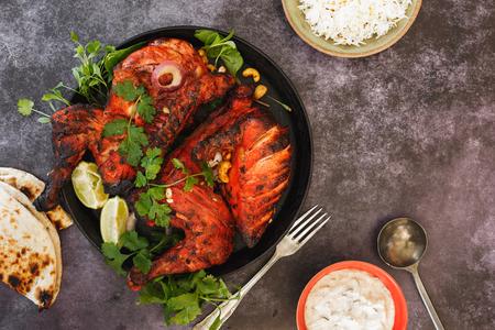 Tandoori Chicken whole with naan, raita and pilau rice, top view, blank space