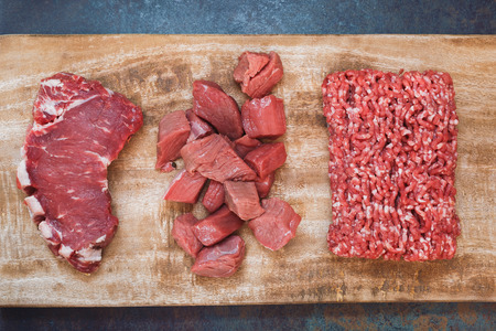 Grass fed raw angus beef meat. Different cuts of raw fresh angus beef meat: sirloin steak, ground and chopped meat on a wooden cutting board