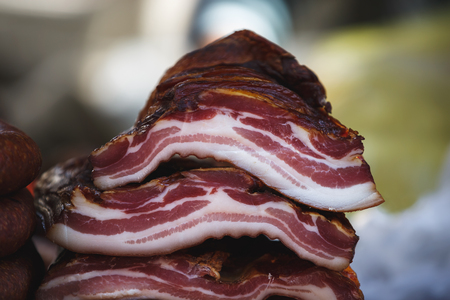 Delicious cold smoked unsliced slab bacon at the meat market, selective focus