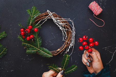Rustic Christmas grapevine wreath. Female hands make Christmas wreath with natural spruce branches. top view, blank space