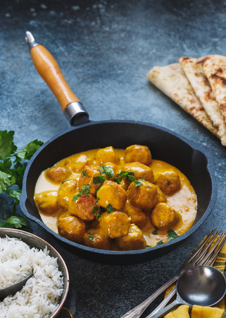 Spicy curry dish with meatballs served with pilau rice and naan bread, selective focus