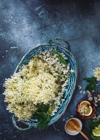 Elderflower syrup in glasses and basket with fresh flowers of elderflowers and acacia on rustic table. Top view, blank space