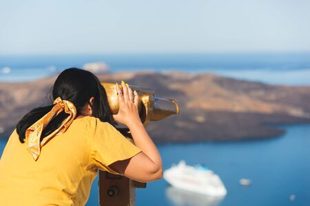 Beautiful young woman looking at cruise ships with binoculars in Thira, Santorini, Greece enjoying vacation, selective focus